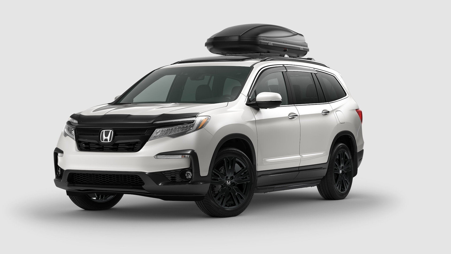 Front 3/4 driver's side view of 2020 Honda Pilot Elite in White Diamond Pearl with Honda Genuine Accessories on roof rack.