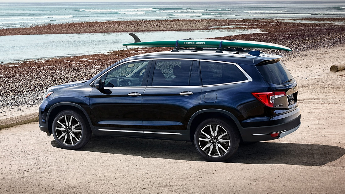 Rear 7/8 driver's side view of 2020 Honda Pilot Touring in Obsidian Blue Pearl with Honda Genuine Accessories on roof rack parked at the beach.