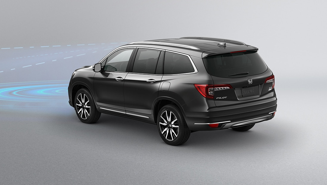 Rear 7/8 driver's side view of 2020 Honda Pilot Elite in Modern Steel Metallic displaying Collision Mitigation Braking System technology.