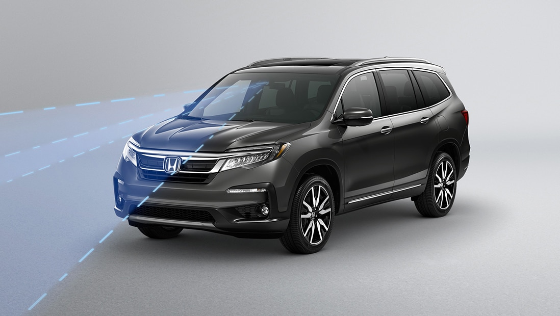Front 3/4 driver's side view of 2020 Honda Pilot Elite in Modern Steel Metallic displaying Road Departure Mitigation technology.