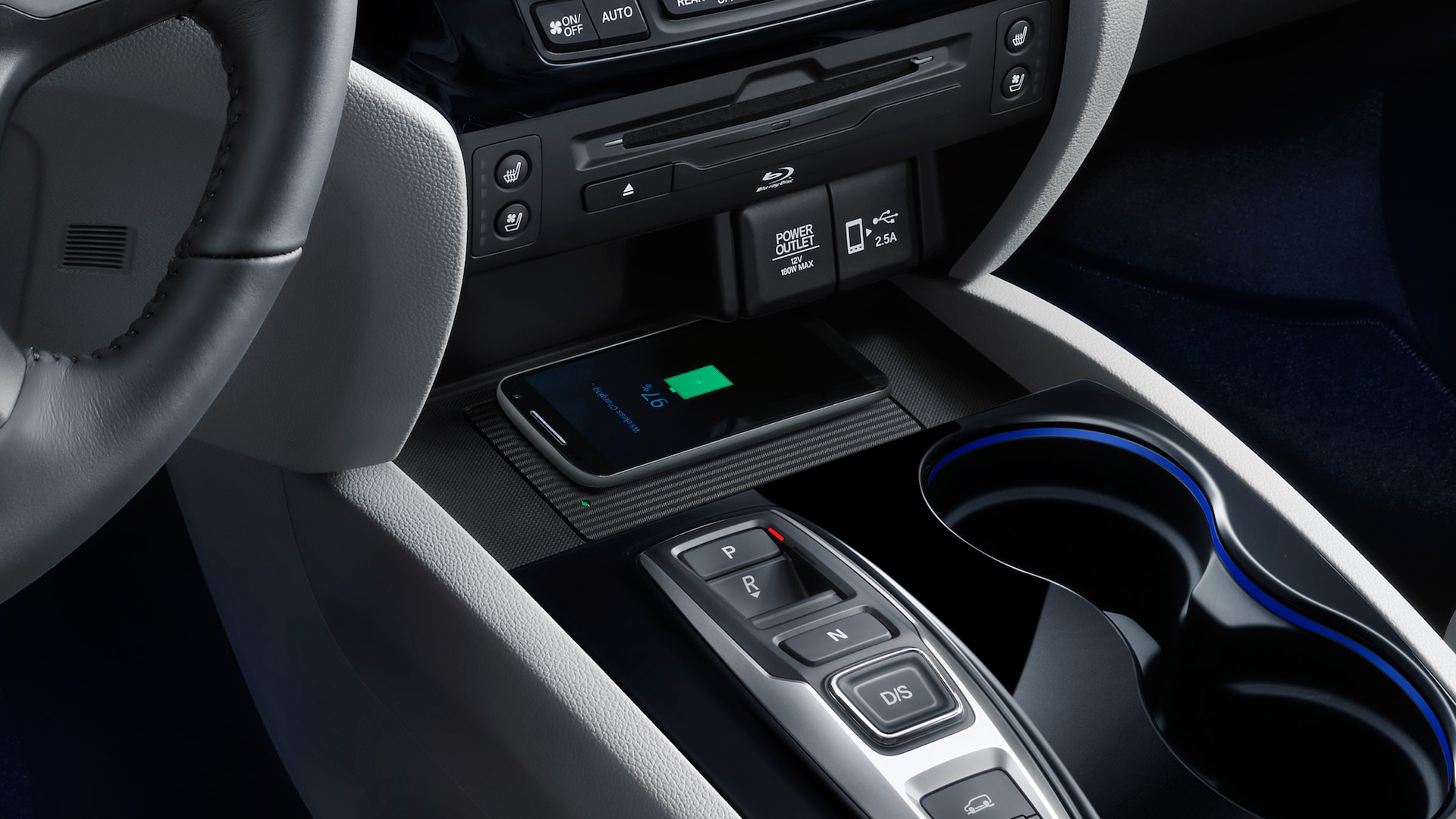 Interior cabin close-up view of wireless phone charging detail in 2020 Honda Pilot Elite with Gray Leather interior.