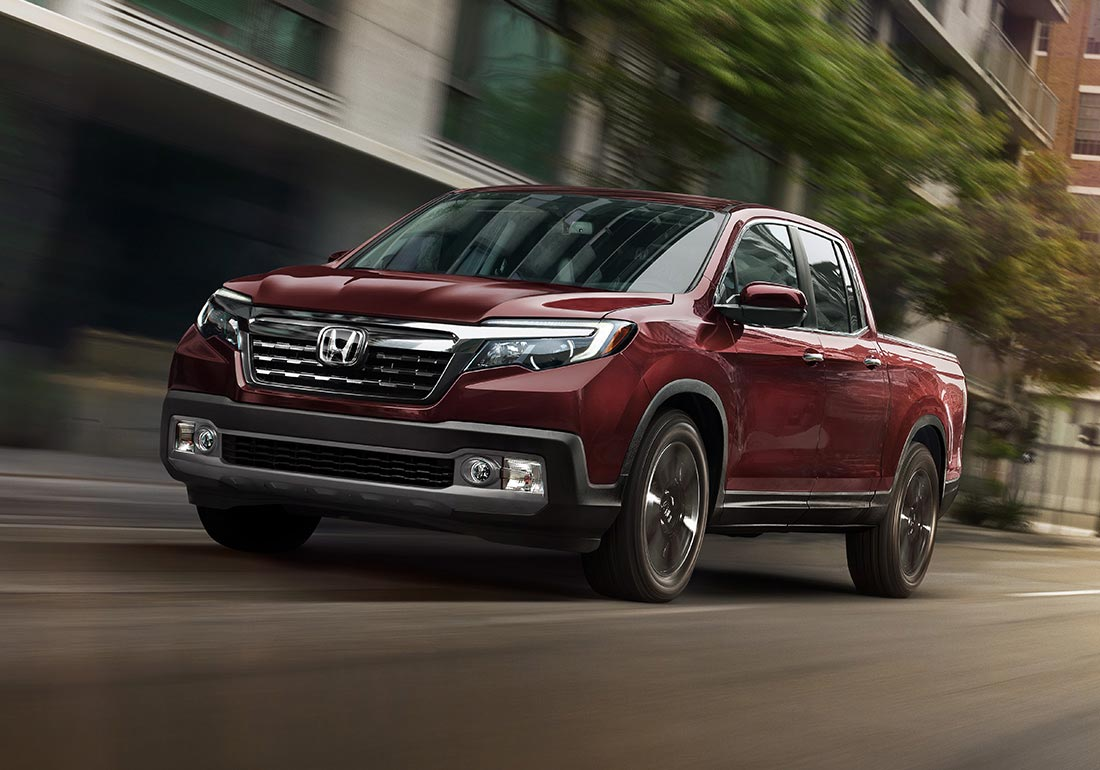 Front driver-side view of 2020 Honda Ridgeline RTL-E in Deep Scarlet Pearl driving on a city street.