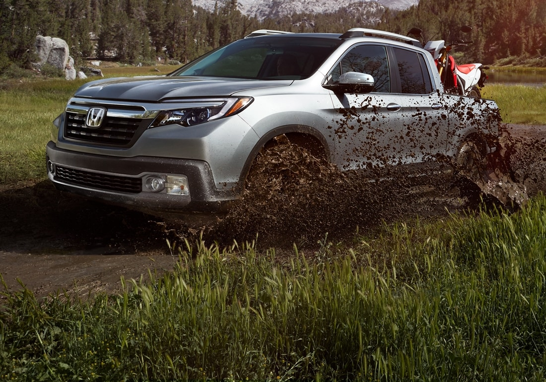 Front driver-side view of 2020 Honda Ridgeline RTL-E in Lunar Silver Metallic driving in mountain environment.