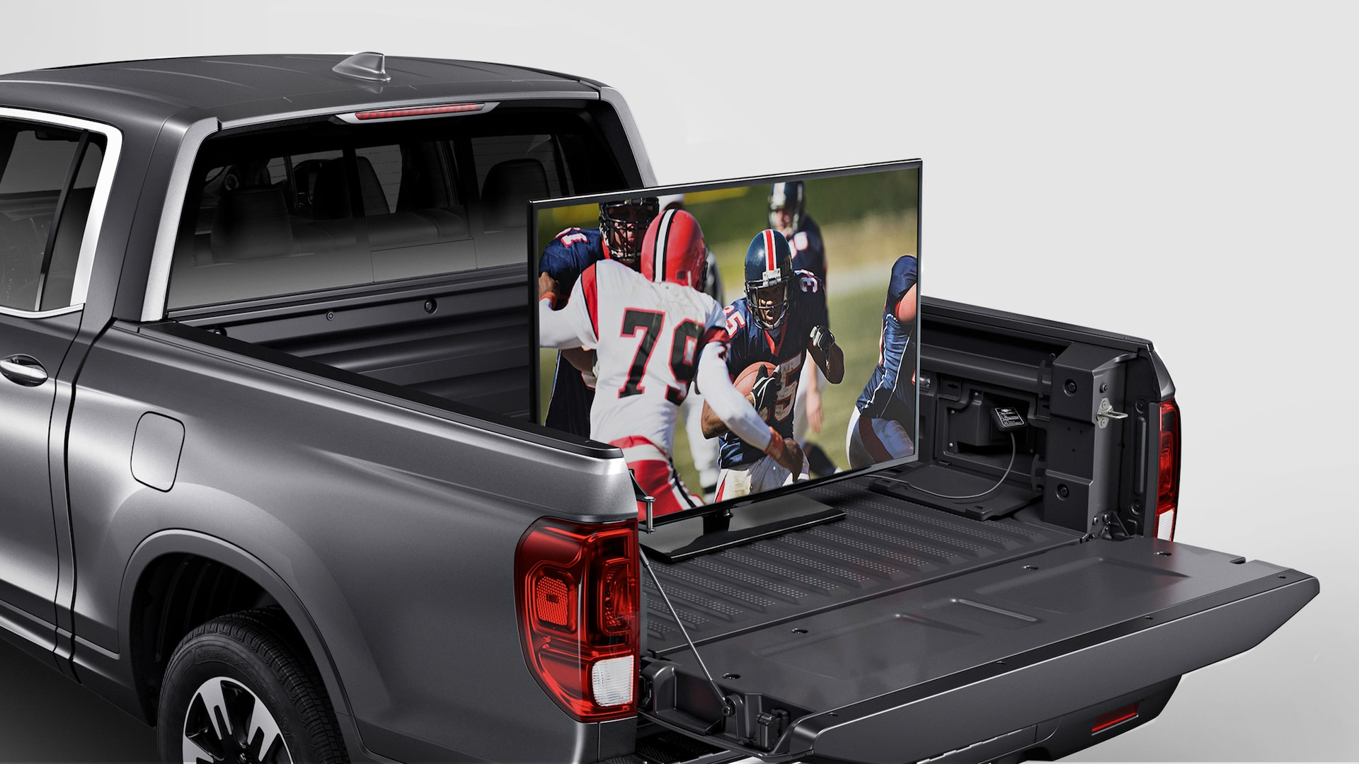 Rear driver-side view of the 2020 Honda Ridgeline RTL-E in Modern Steel Metallic storing TV in truck bed.