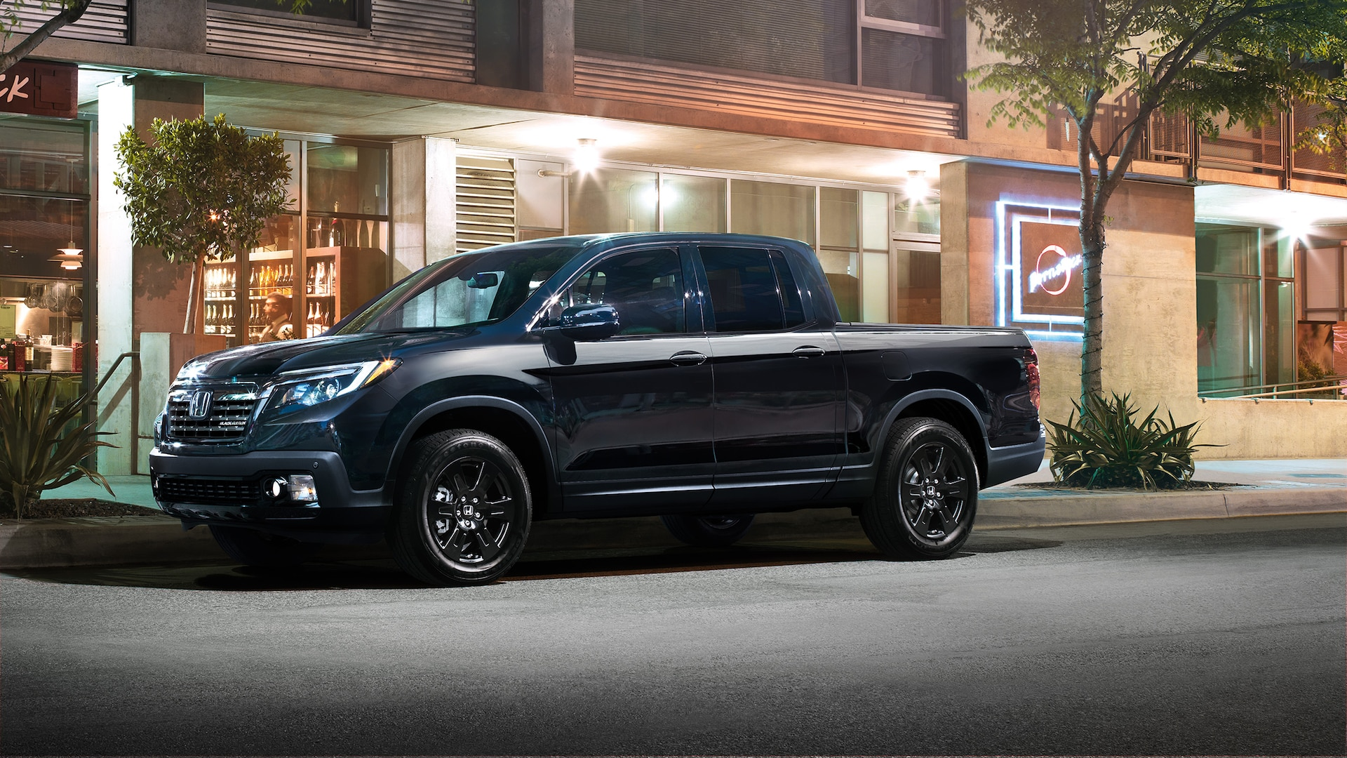 Driver-side view of the 2020 Honda Ridgeline Black Edition in Crystal Black Pearl parked in front of restaurant.