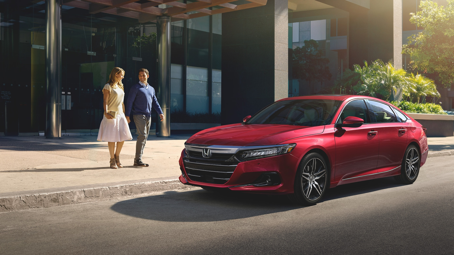 Front three-quarter driver-side view of the 2021 Accord Touring 2.0T, shown in Radiant Red Metallic, parked in an urban environment and with a young couple approaching.
