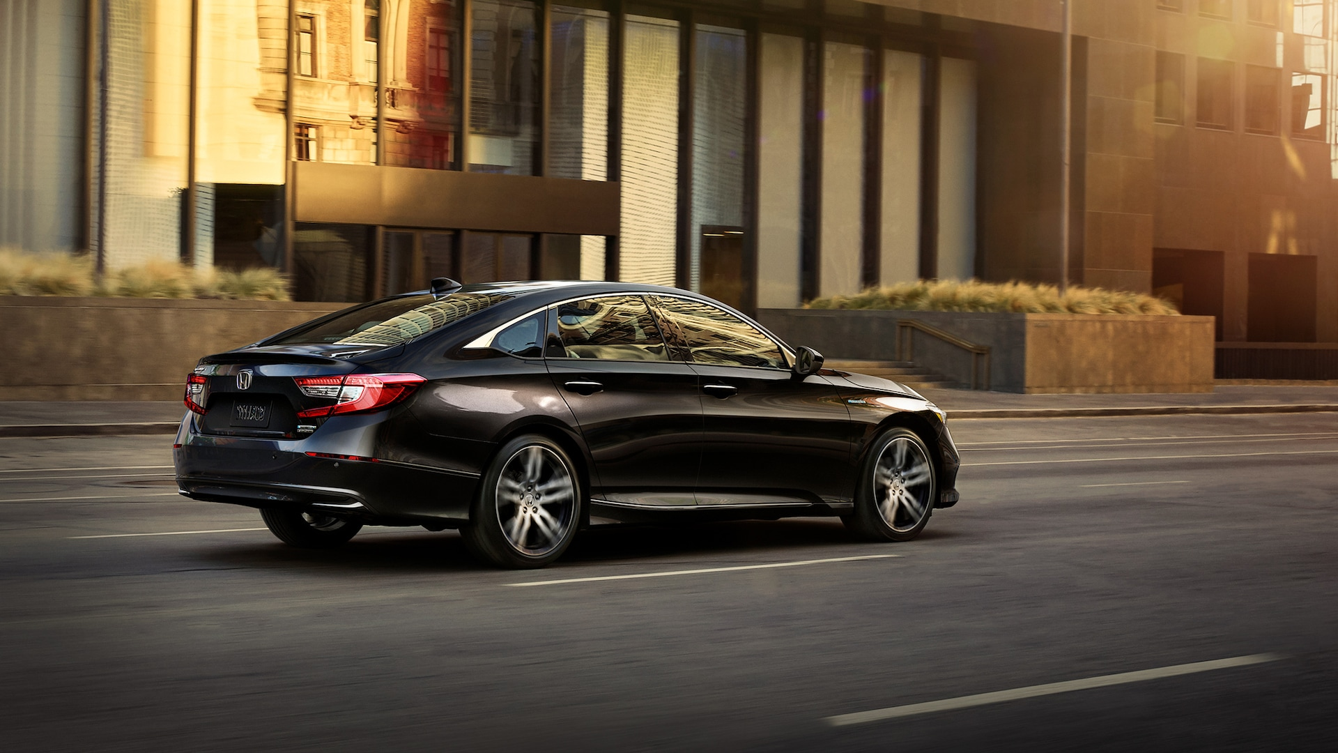 Oblique passenger-side view of the 2021 Accord Hybrid, shown in Crystal Black Pearl, driving through an urban city environment at sunset.