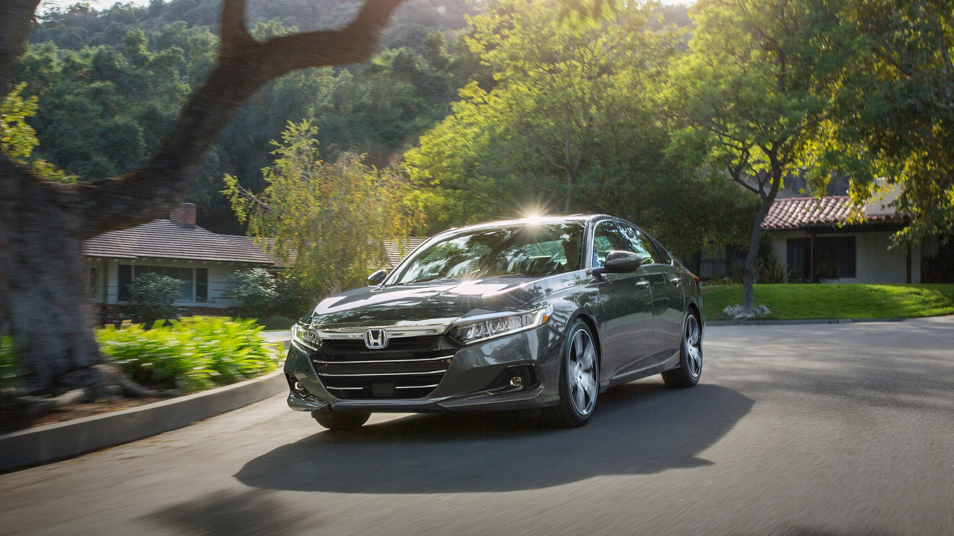 Front driver-side view of the 2021 Honda Accord Hybrid Touring in Modern Steel Metallic, driving through residential neighborhood.