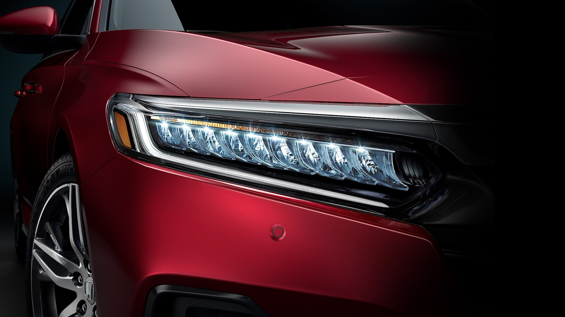 Front detail of the 2021 Accord Touring 2.0T, shown in Radiant Red Metallic, with a focus on the LED headlights.