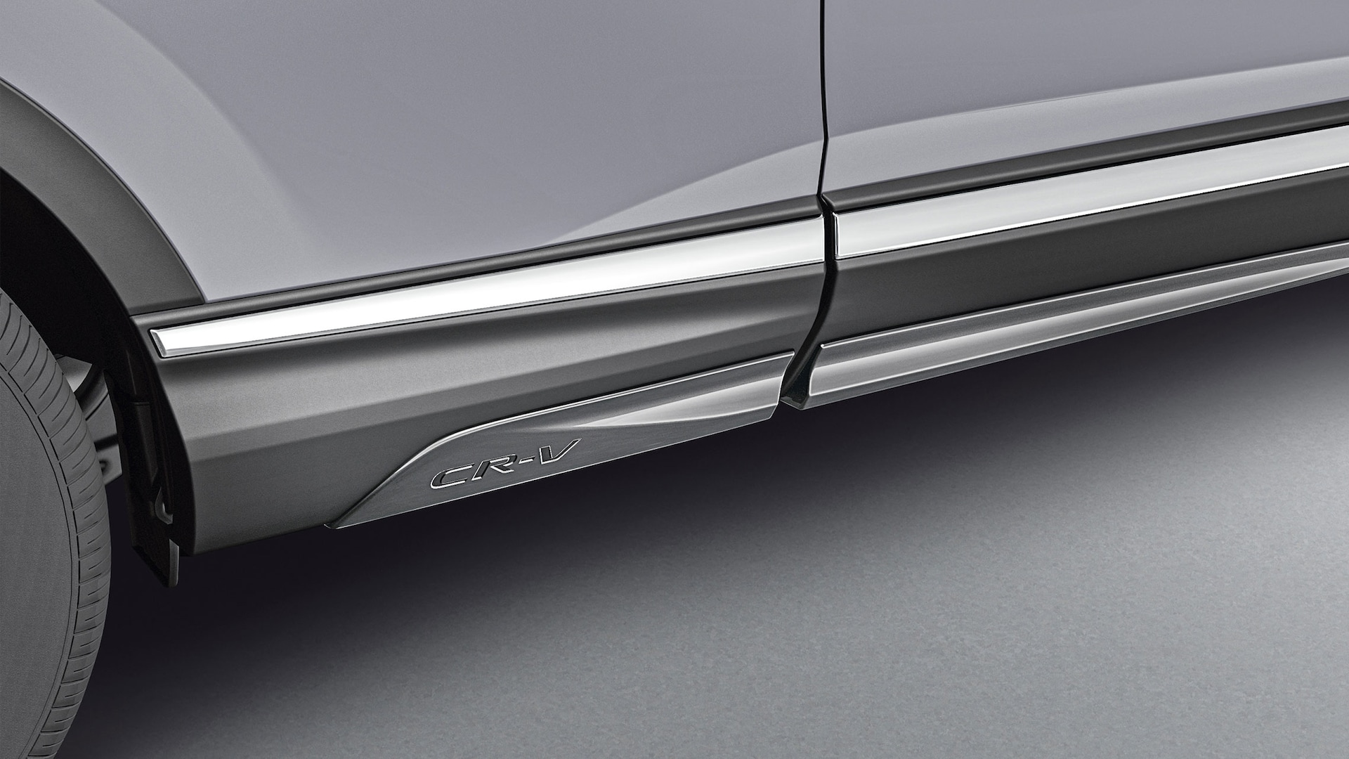 Detail of accessory gloss-black side lower trim on the 2021 Honda CR-V in Sonic Gray Pearl.