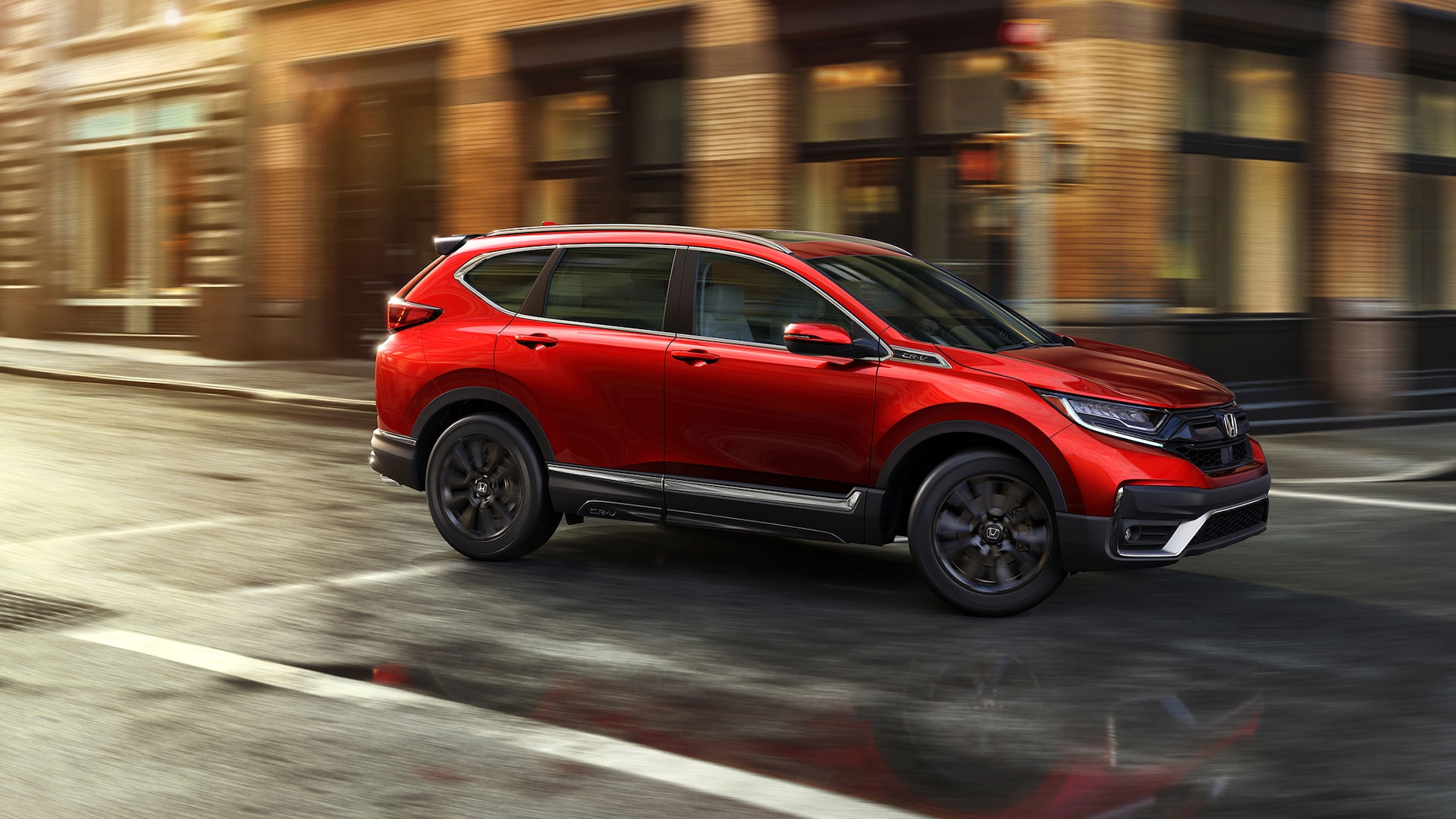 Front passenger-side view of the 2021 Honda CR-V Touring in Radiant Red Metallic with Honda Genuine Accessories, driving in an urban environment.