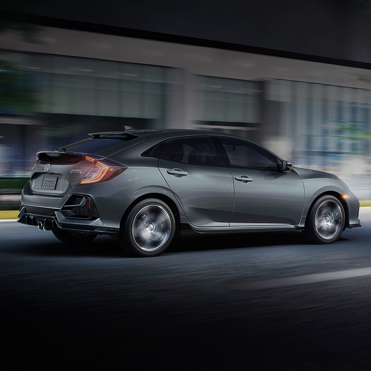 Rear passenger-side view of the 2021 Honda Civic Sport Touring Hatchback, in Sonic Gray Pearl, driving in city at night.