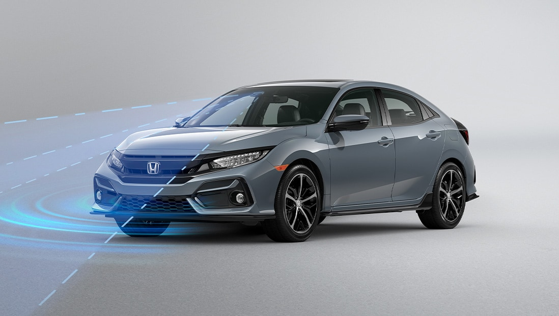 Front driver-side view of the 2021 Honda Civic Sport Touring Hatchback in Sonic Gray Pearl, demonstrating Road Departure Mitigation System.