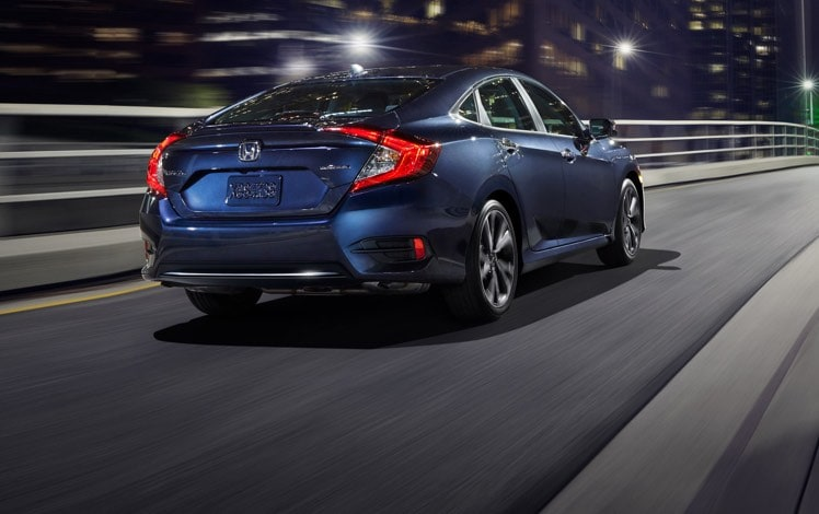 Rear passenger-side three-quarter view of the 2021 Honda Civic Touring Sedan in Cosmic Blue Metallic driving over a bridge at night.