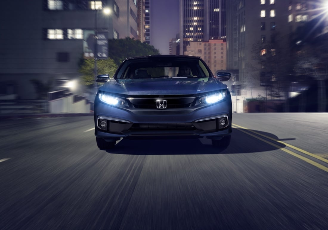 Head-on view of the 2021 Honda Civic Touring Sedan in Cosmic Blue Metallic driving through an urban environment at night.