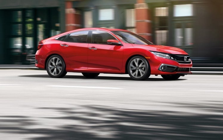 Passenger-side view of the 2021 Honda Civic Touring Sedan in Rallye Red driving through an urban center.