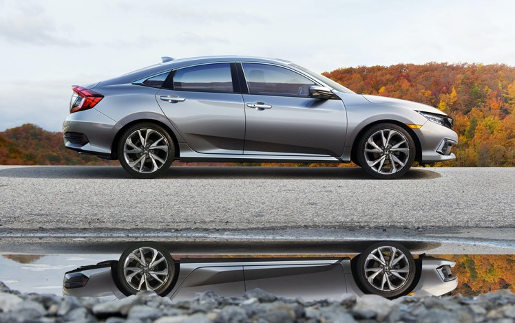 Passenger-side profile view of the 2021 Honda Civic Touring Sedan in Lunar Silver Metallic shown on a rural road in front of autumnal trees.