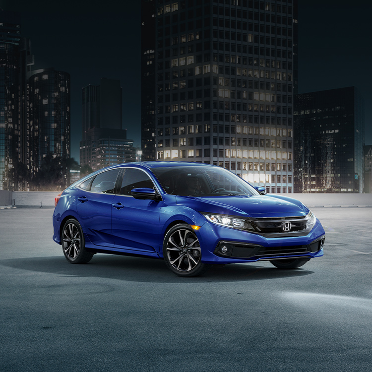 Front three-quarter passenger-side view of the 2021 Honda Civic Sedan Sport, shown in Aegean Blue Metallic, in an empty parking lot in front of an urban cityscape at night.