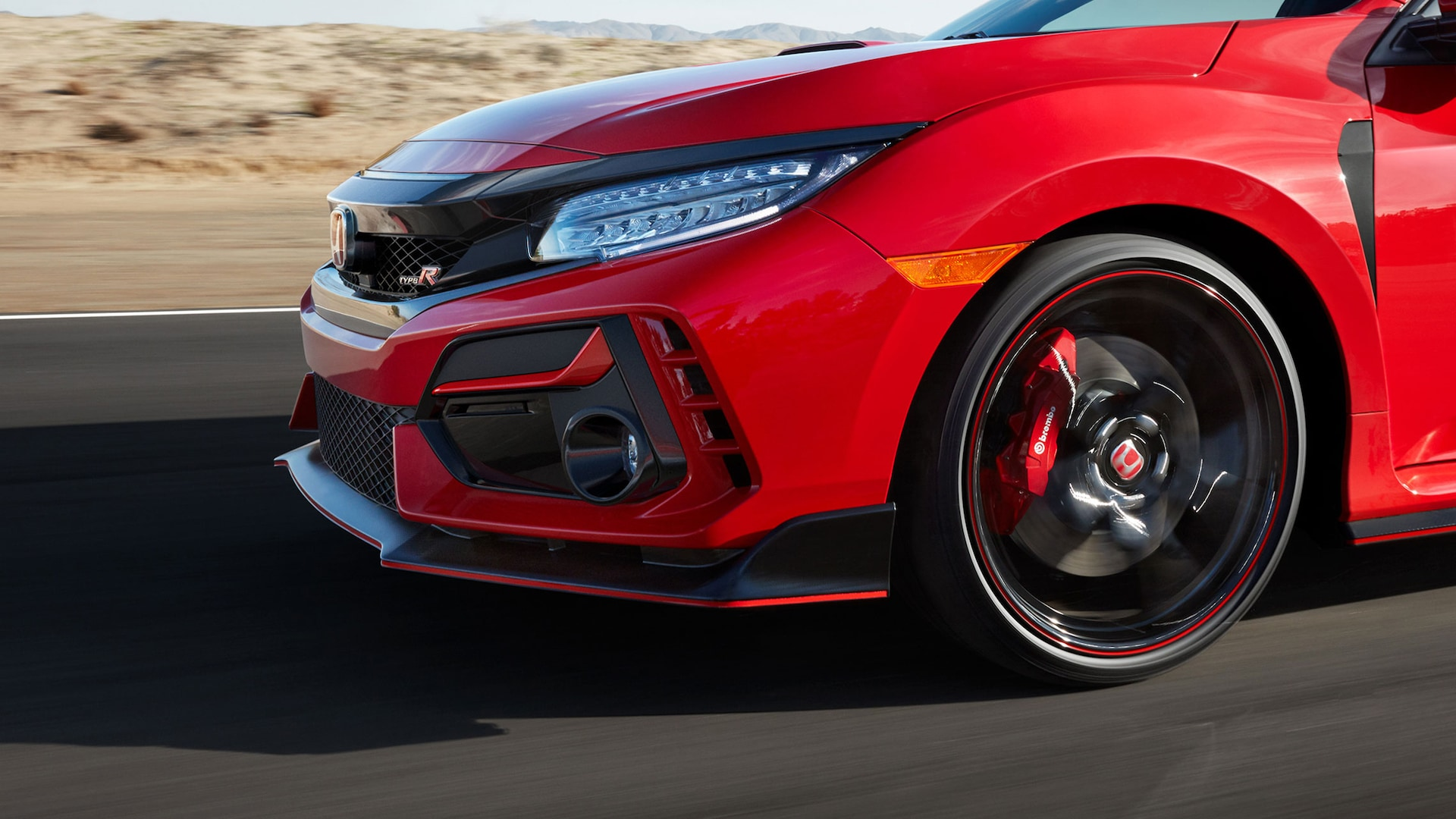 Front driver-side view of the 2021 Honda Civic Type R in Rallye Red, driving on desert racetrack.
