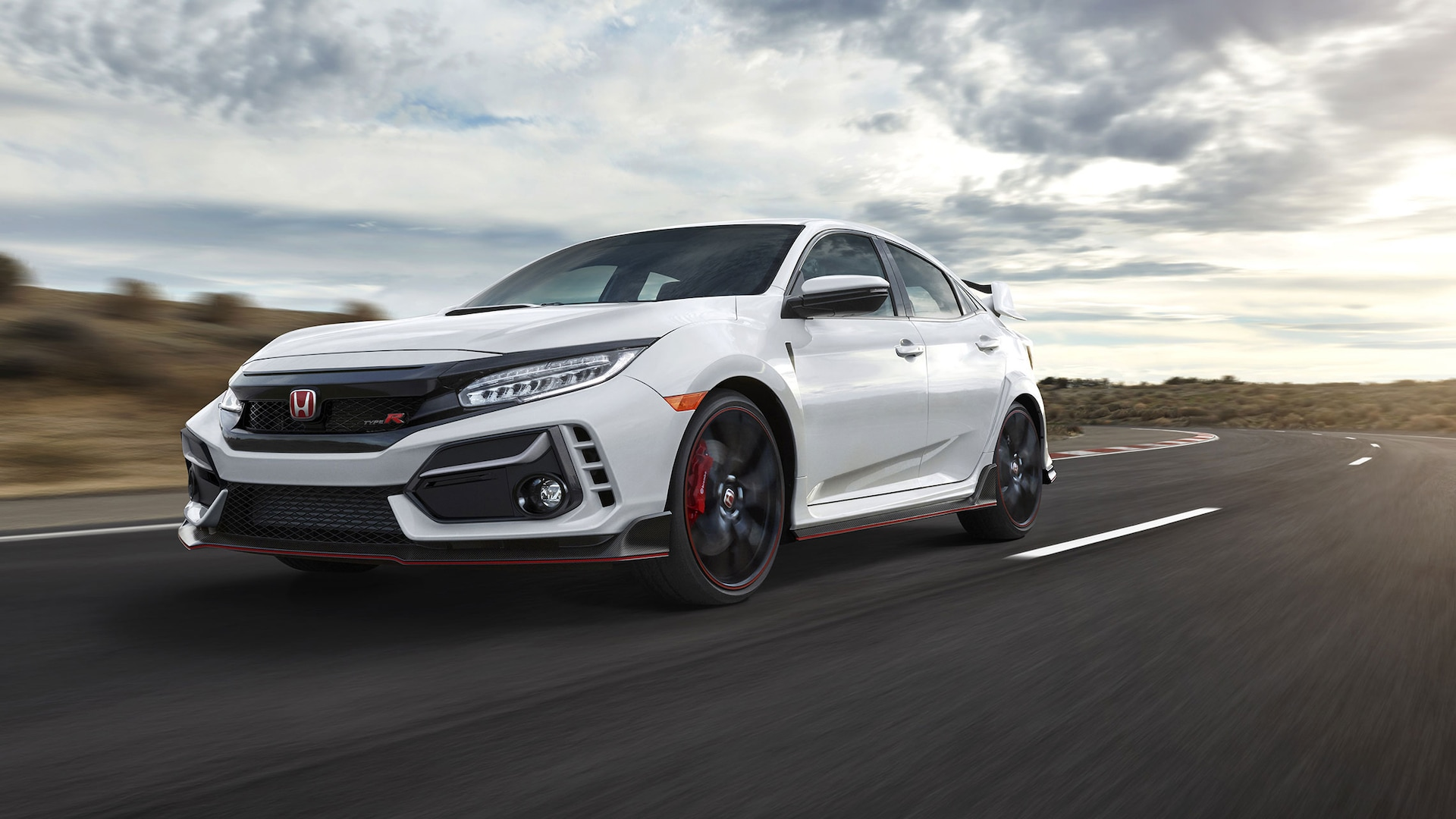 Front driver-side view of the 2021 Honda Civic Type R in Championship White, driving on a racetrack.