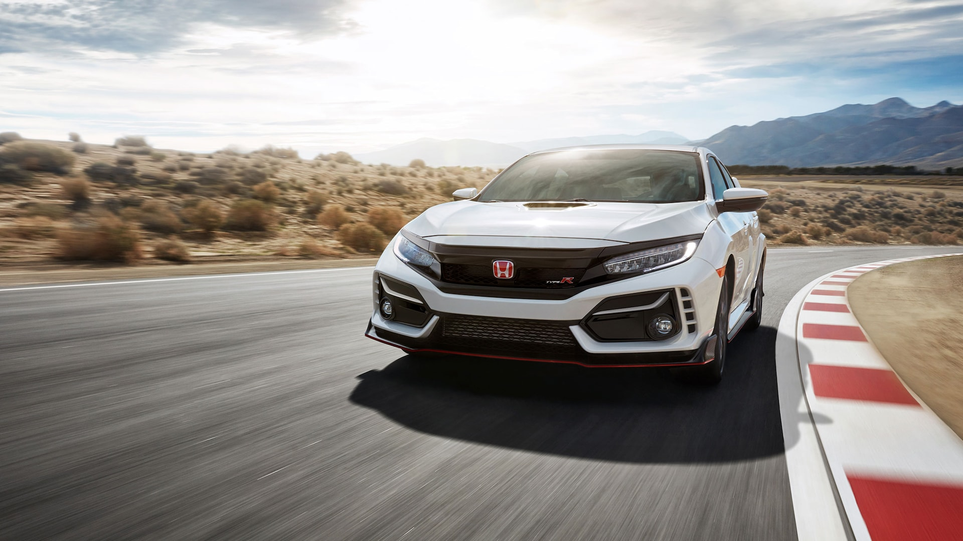 Front view of the 2021 Honda Civic Type R in Championship White, driving on desert racetrack.