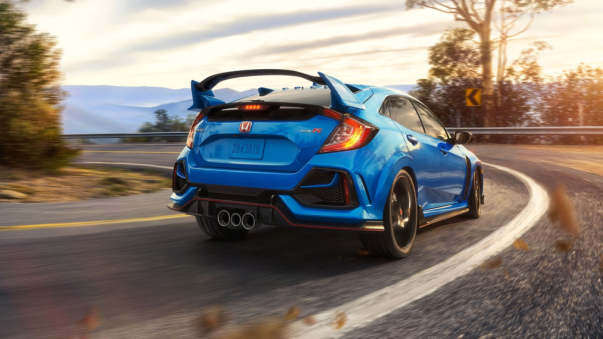 Rear passenger-side view of the 2021 Honda Civic Type R in Boost Blue Pearl, driving on a mountain road.