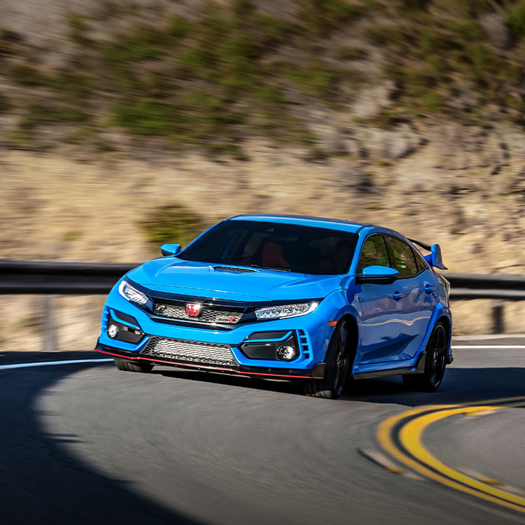 Front driver-side view of the 2021 Honda Civic Type R in Boost Blue Pearl, driving on a mountain road.