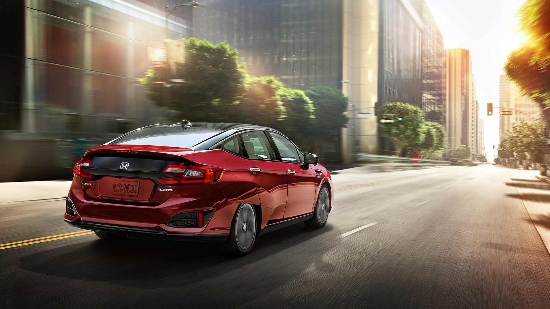 Rear passenger-side view of the 2021 Honda Clarity Fuel Cell in Crimson Pearl driving on a city street.