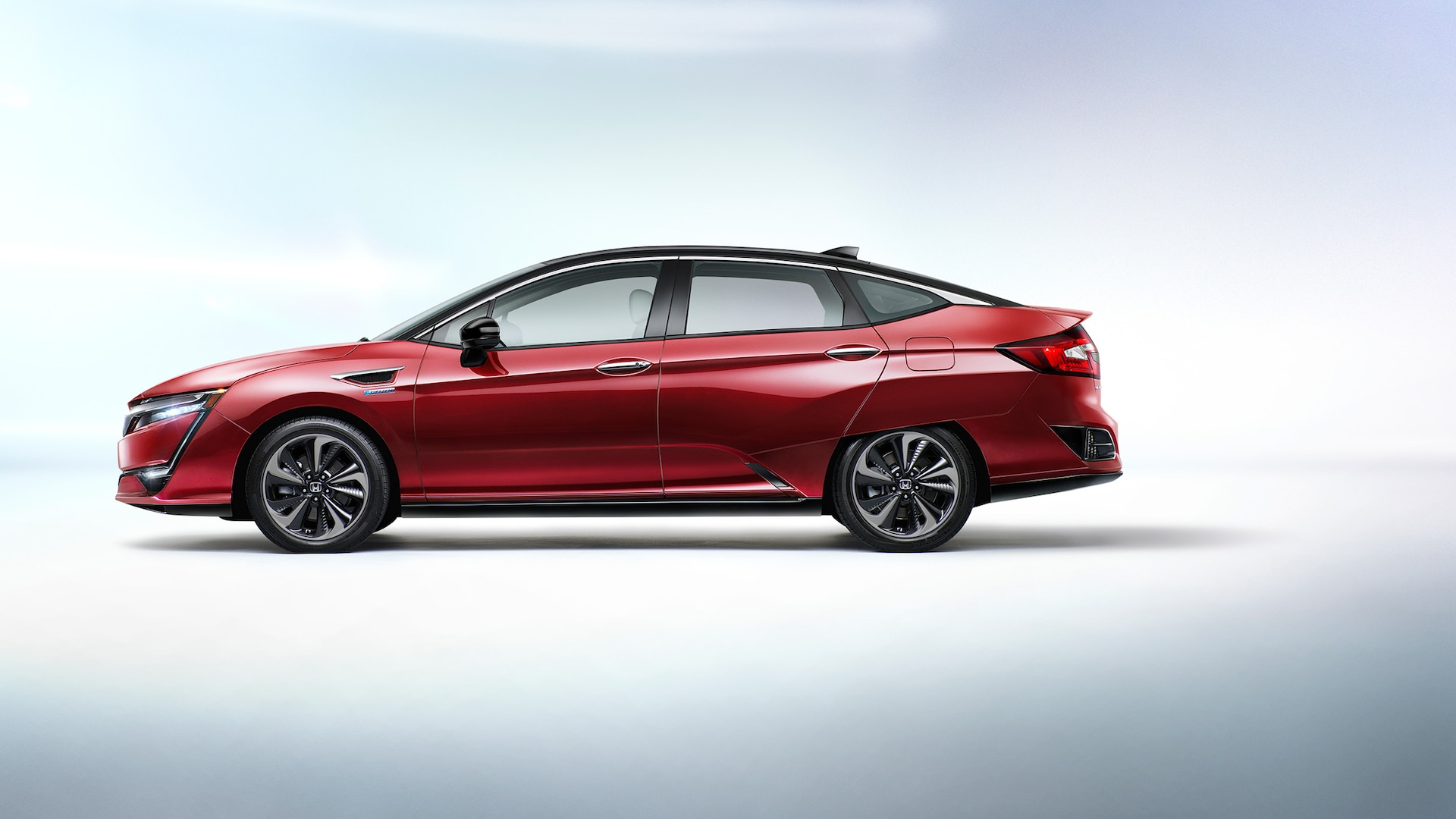 Side profile of 2021 Honda Clarity Fuel Cell in Crimson Pearl.