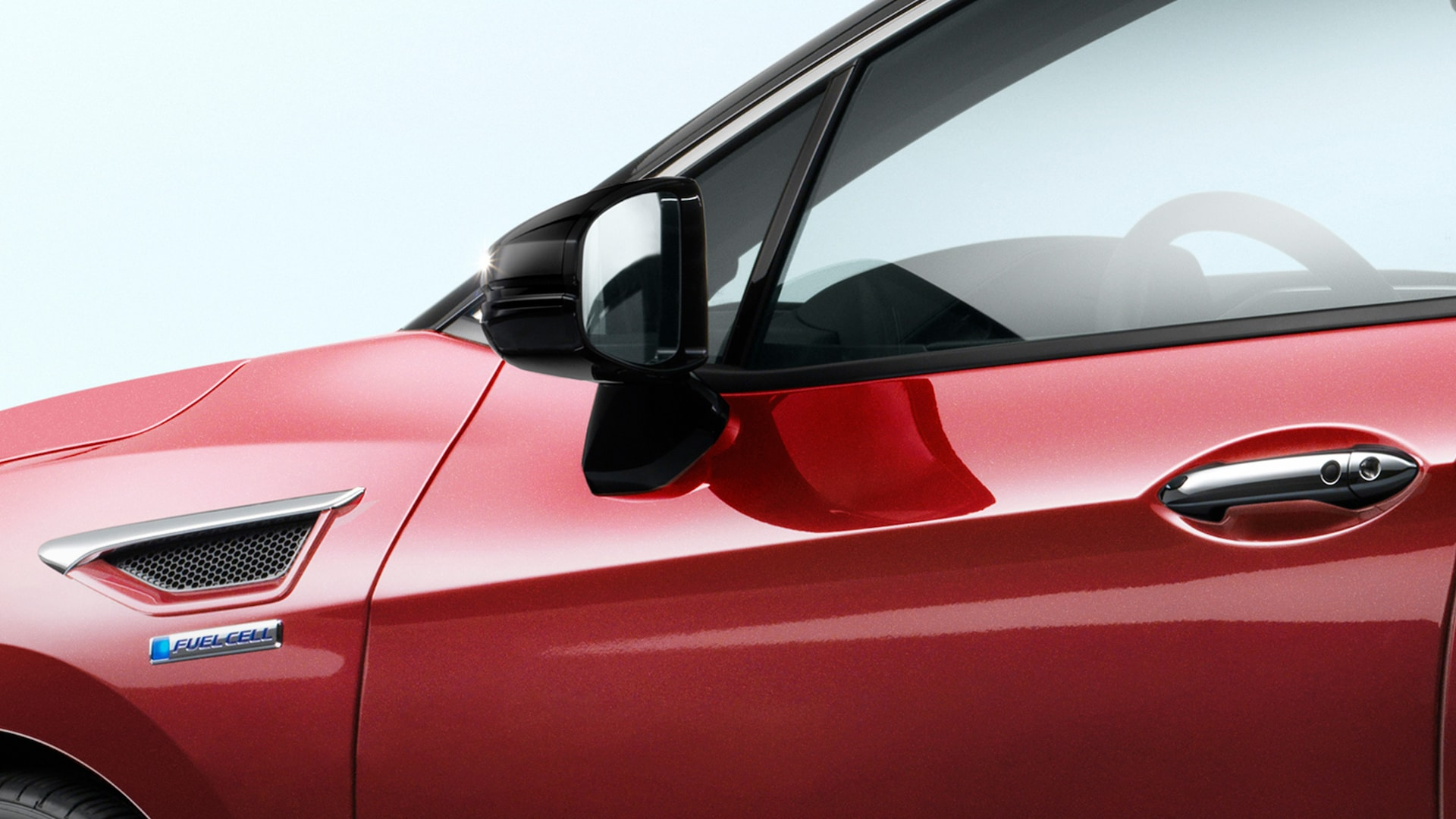 Detail of the heated side rear view mirrors on the 2021 Honda Clarity Fuel Cell in Crimson Pearl.