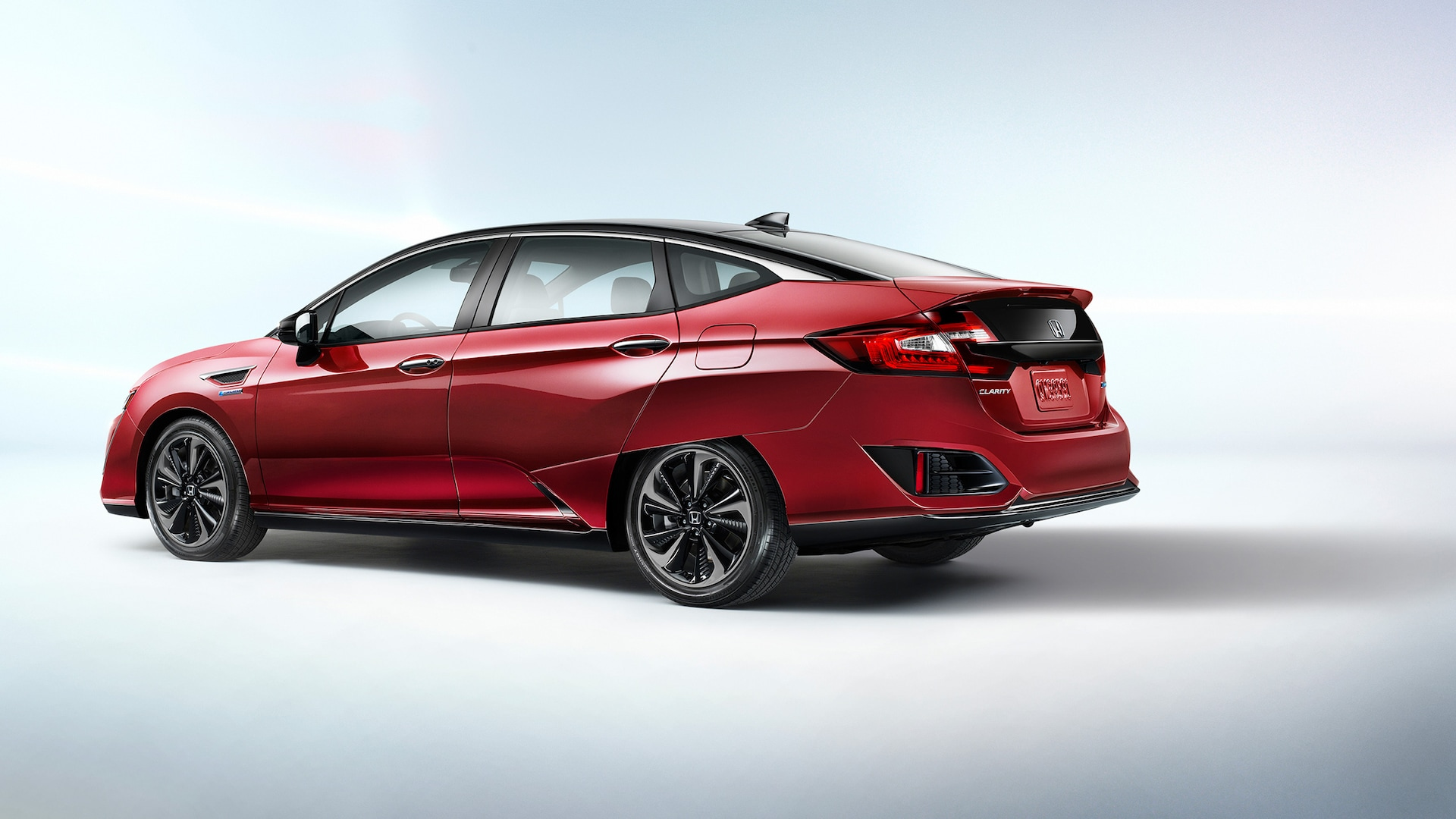 Rear driver-side view of 2021 Honda Clarity Fuel Cell in Crimson Pearl.