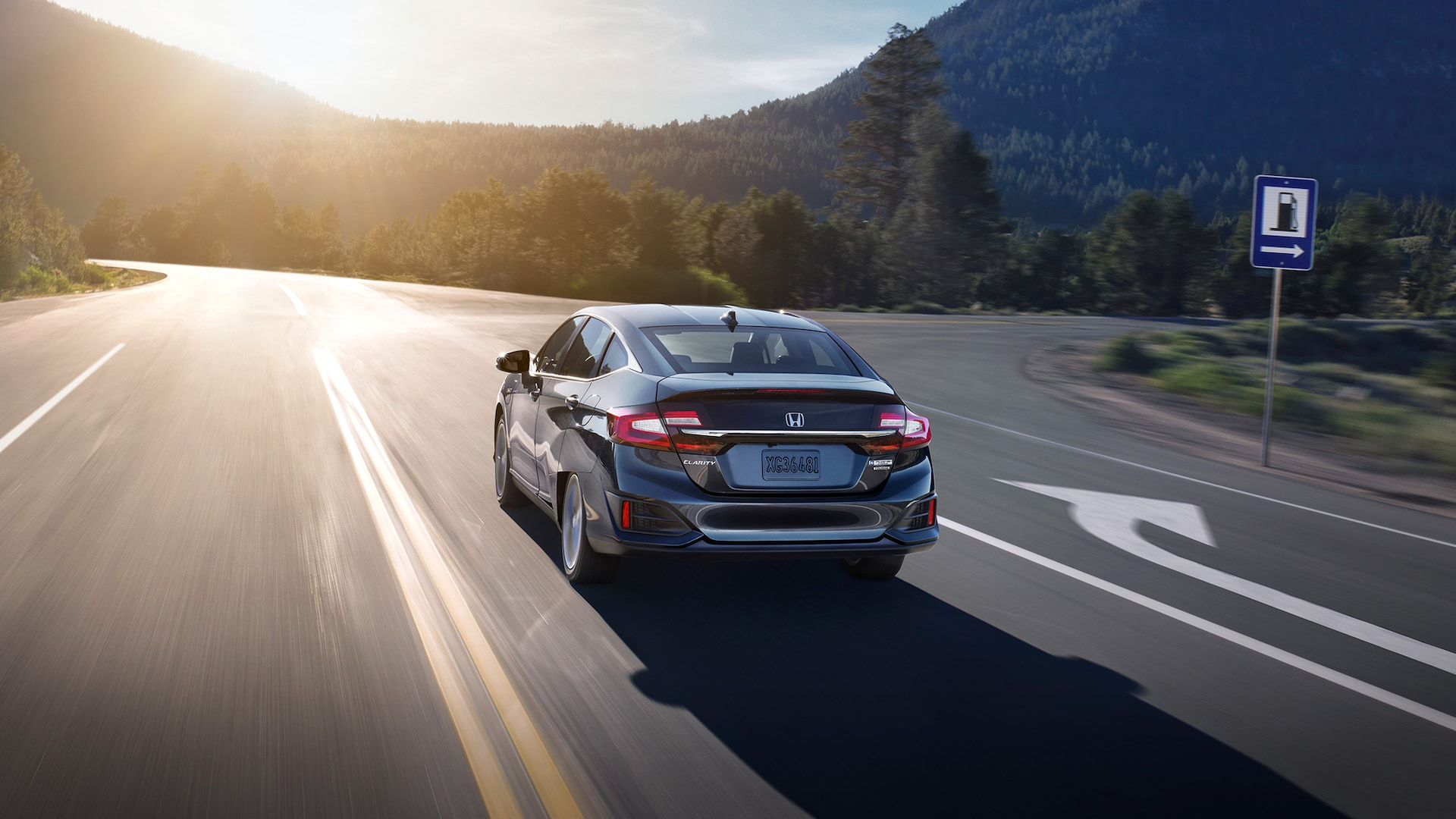 Rear of 2021 Clarity Plug-In Hybrid in Modern Steel Metallic driving along tree-lined road.