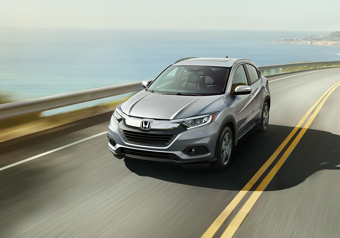 Front driver-side view of the 2021 Honda HR-V EX-L in Lunar Silver Metallic driving past a body of water.