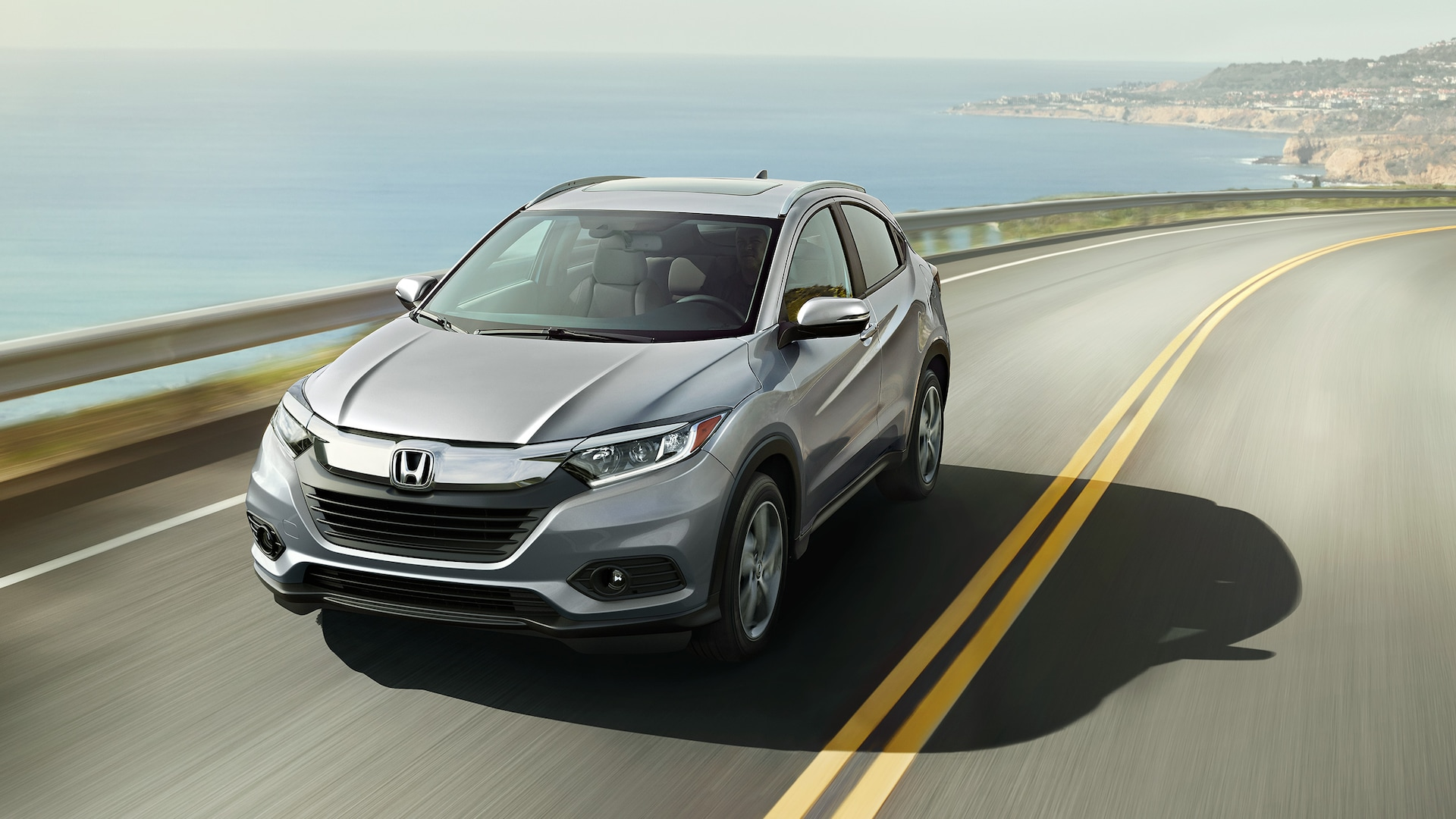 Front driver-side view of the 2021 Honda HR-V EX-L in Lunar Silver Metallic driving on a highway overlooking an ocean.