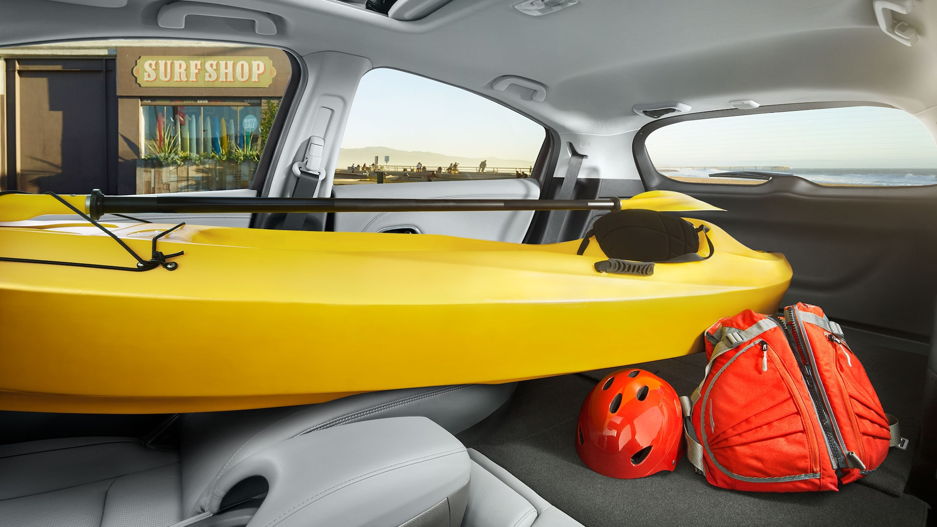 Interior view of the 2021 Honda HR-V EX-L with Gray Leather, with all rear seats and passenger seat folded down, storing a kayak and luggage.