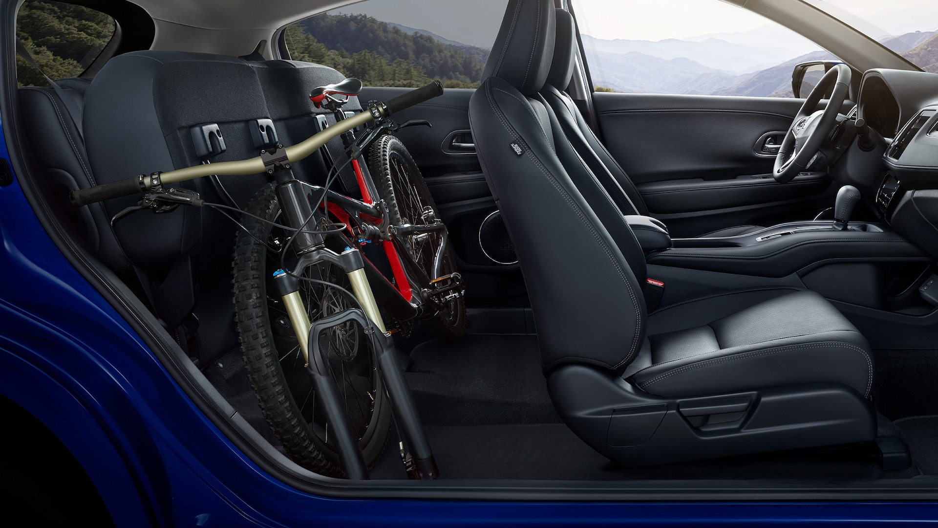 Interior passenger-side view of the 2021 Honda HR-V EX-L with Black Leather, with folded rear seats, stowing a bike.