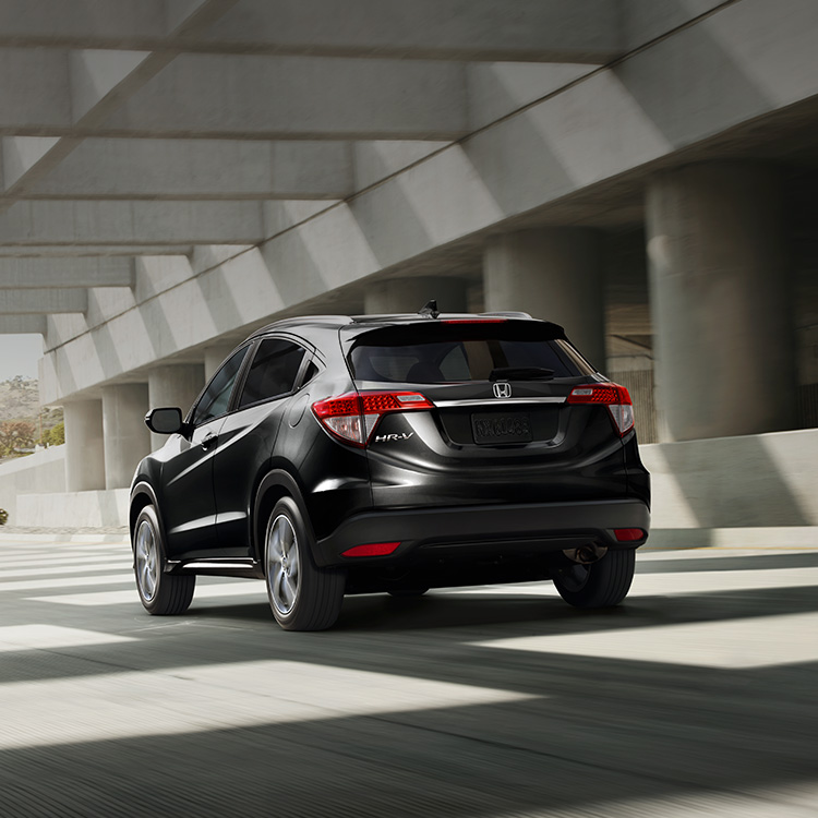 Rear driver-side view of the 2021 Honda HR-V EX-L in Crystal Black Pearl driving on a highway.