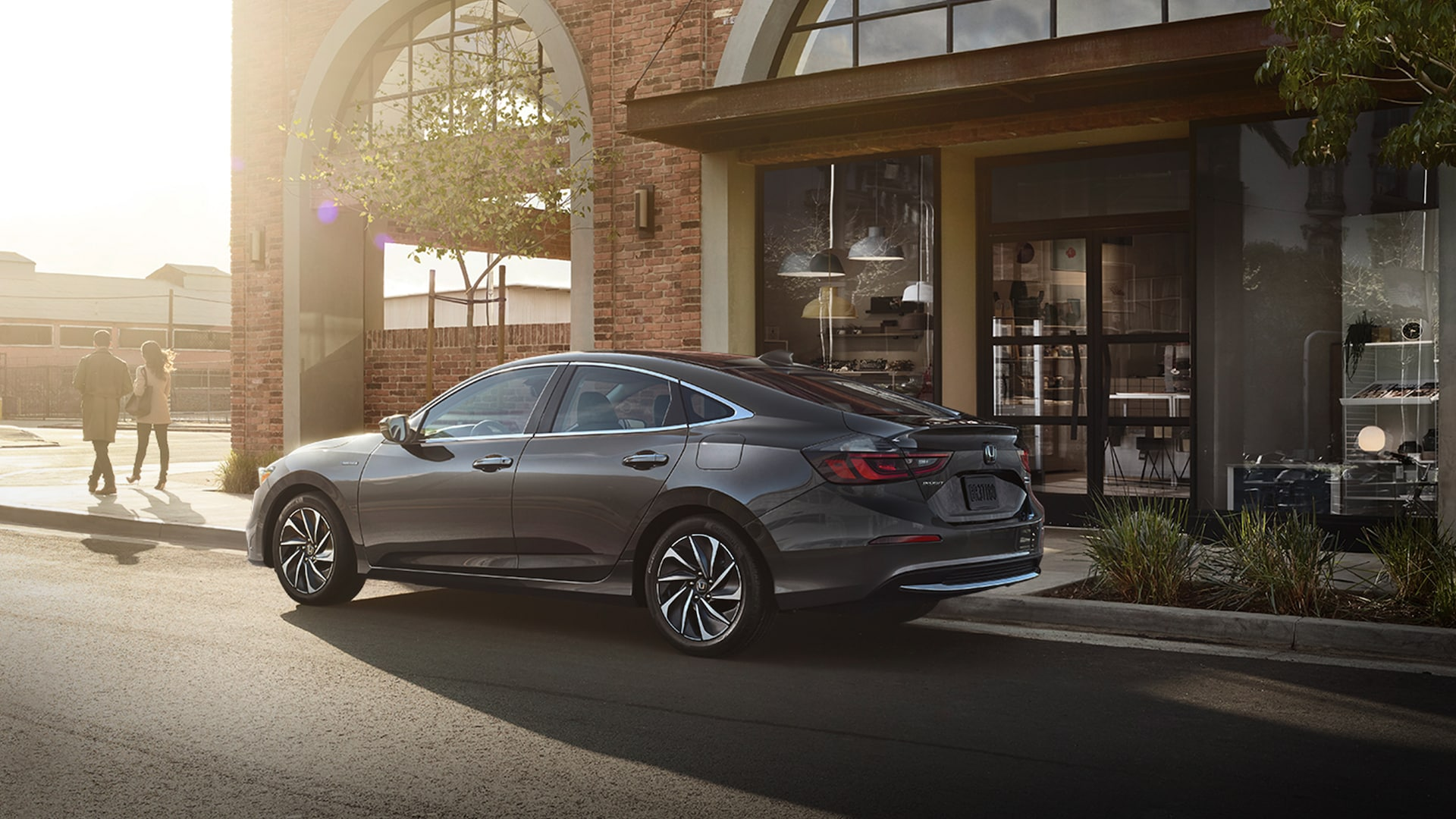 Driver-side profile view of 2021 Honda Insight Touring in Modern Steel Metallic parked in front of modern home.