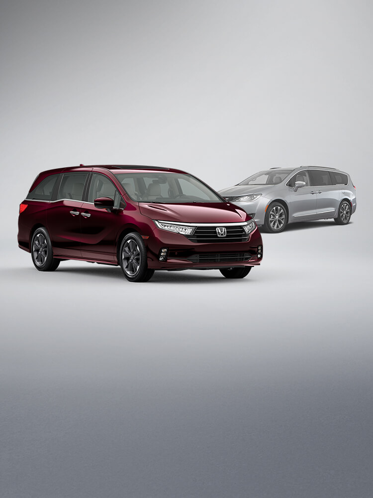 Front passenger-side view of the 2021 Honda Odyssey Elite in Deep Scarlet Pearl parked in front of the 2020 Chrysler Pacifica.