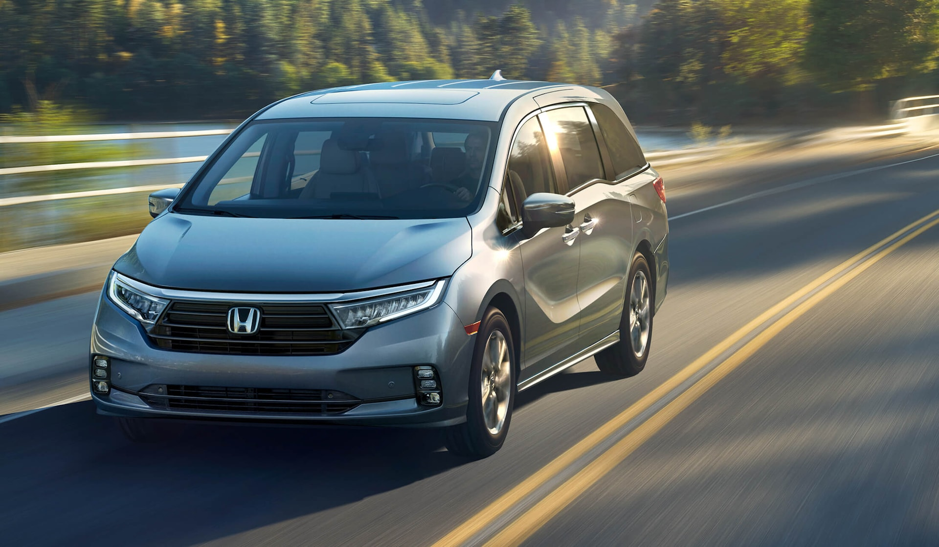 Front driver-side view of the 2022 Honda Odyssey Elite in Lunar Silver Metallic driving in forest environment.
