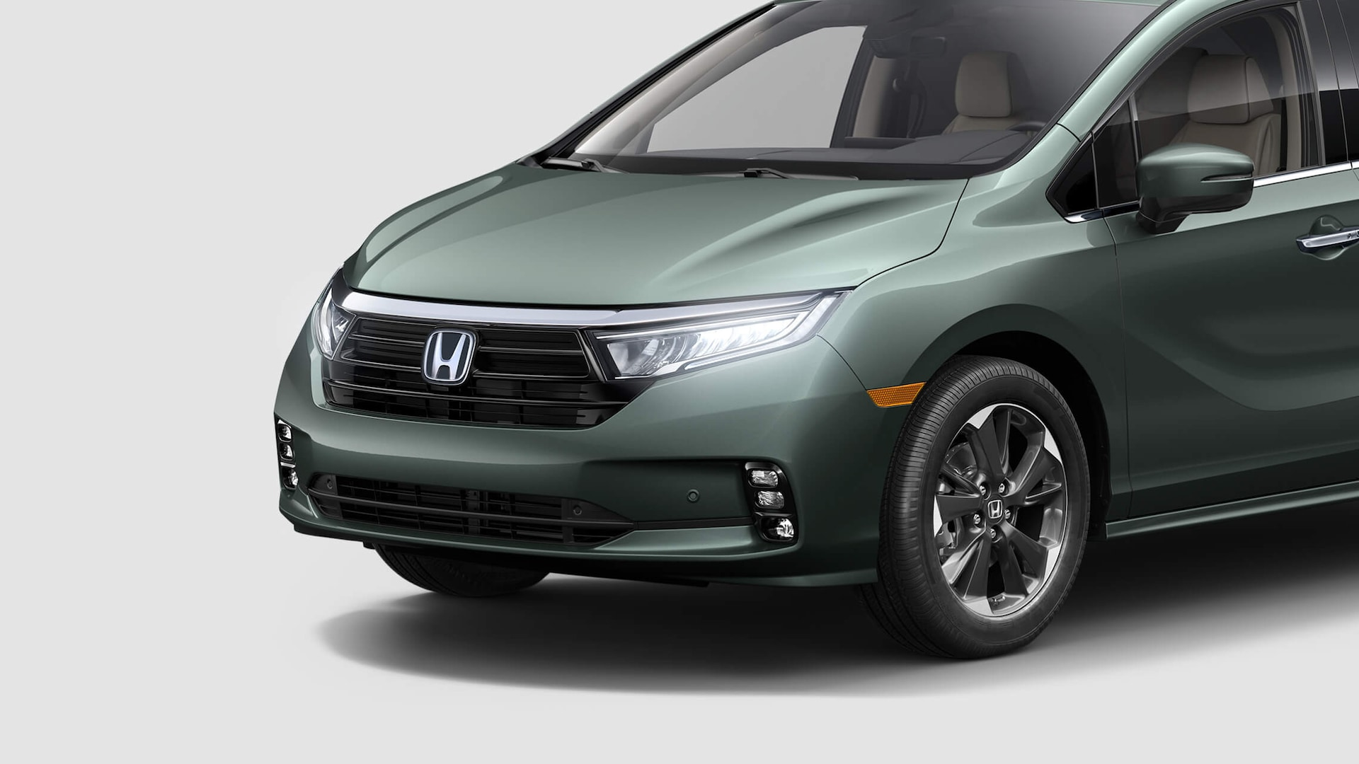 Front driver-side close-up of headlights on the 2021 Honda Odyssey Elite in Forest Mist Metallic.
