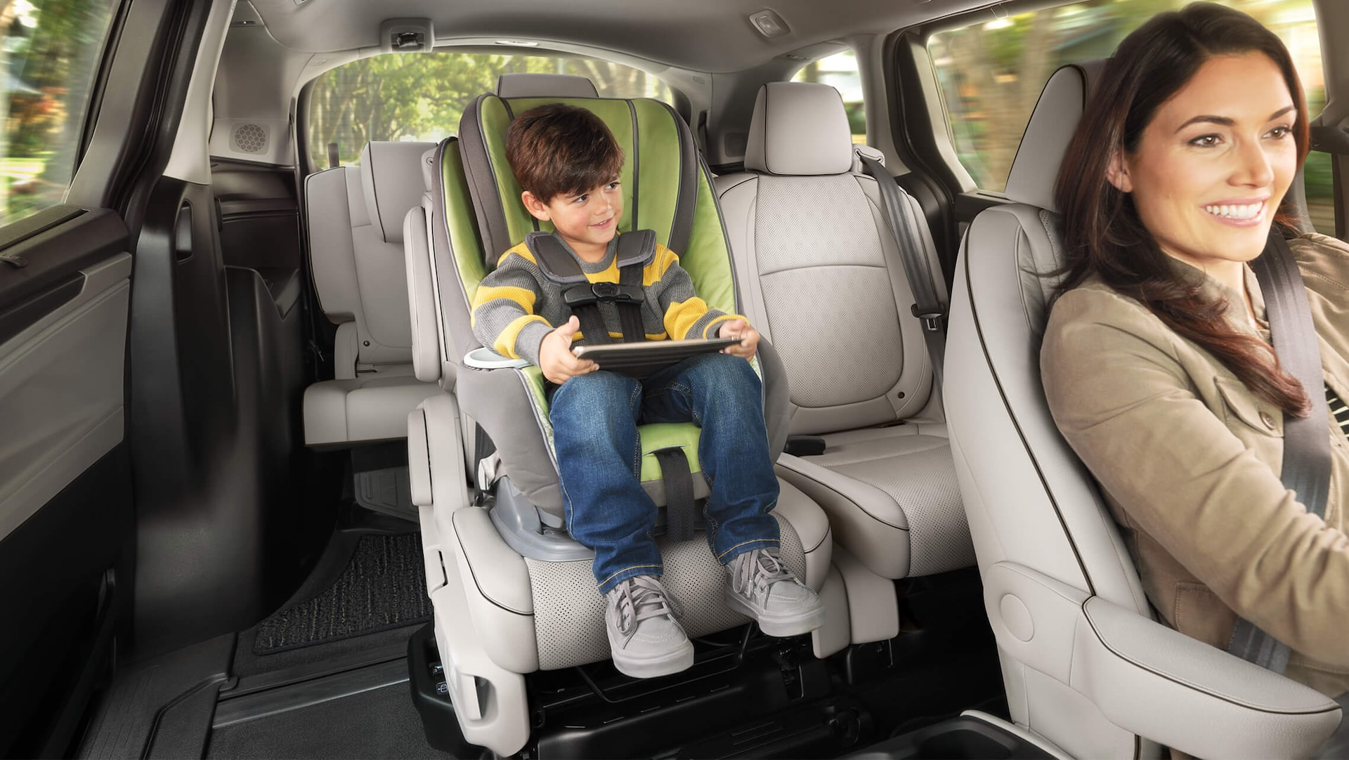 Interior view of Magic Slide® 2nd-row seats, with woman driving and child in rear car seat, in the 2022 Honda Odyssey Elite with Gray Leather.