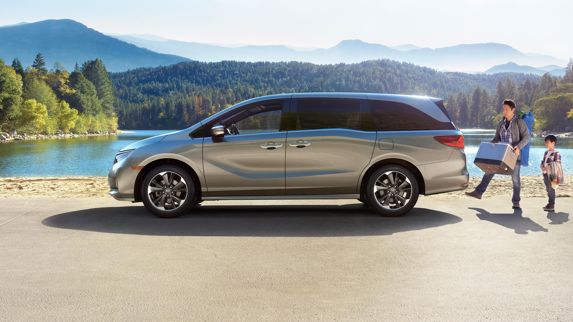 Driver-side profile view of the 2022 Honda Odyssey Touring in Lunar Silver Metallic parked in forest environment.