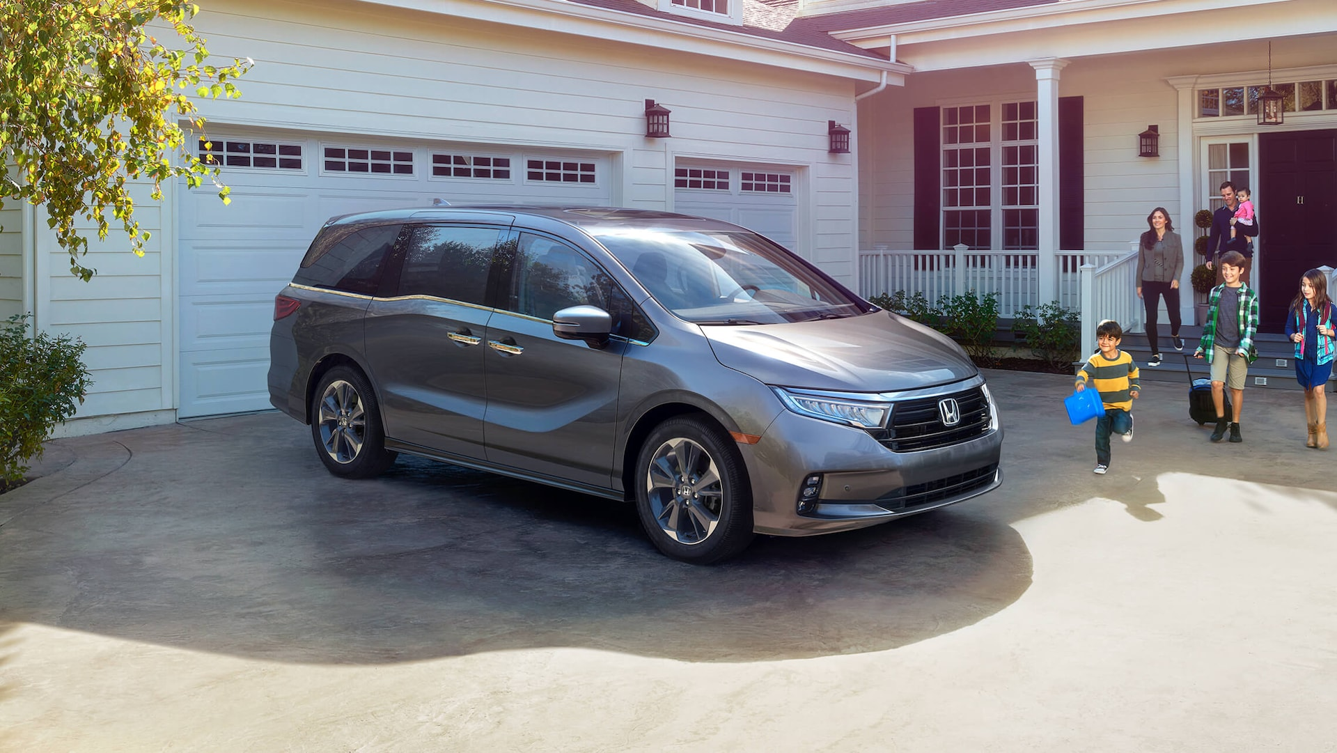 Front passenger-side view of the 2022 Honda Odyssey EX in Deep Scarlet Pearl parked in front of house.