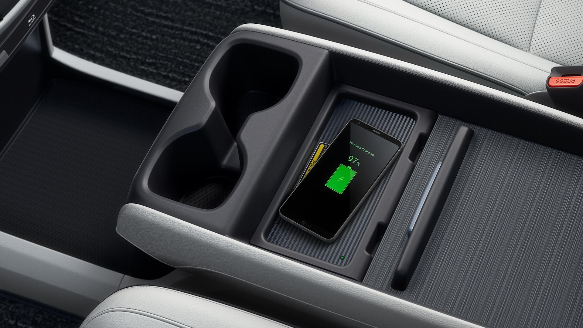 Interior overhead close-up view of center console in the 2022 Honda Odyssey Elite with Beige Leather, with mobile phone charging on the wireless phone charger.