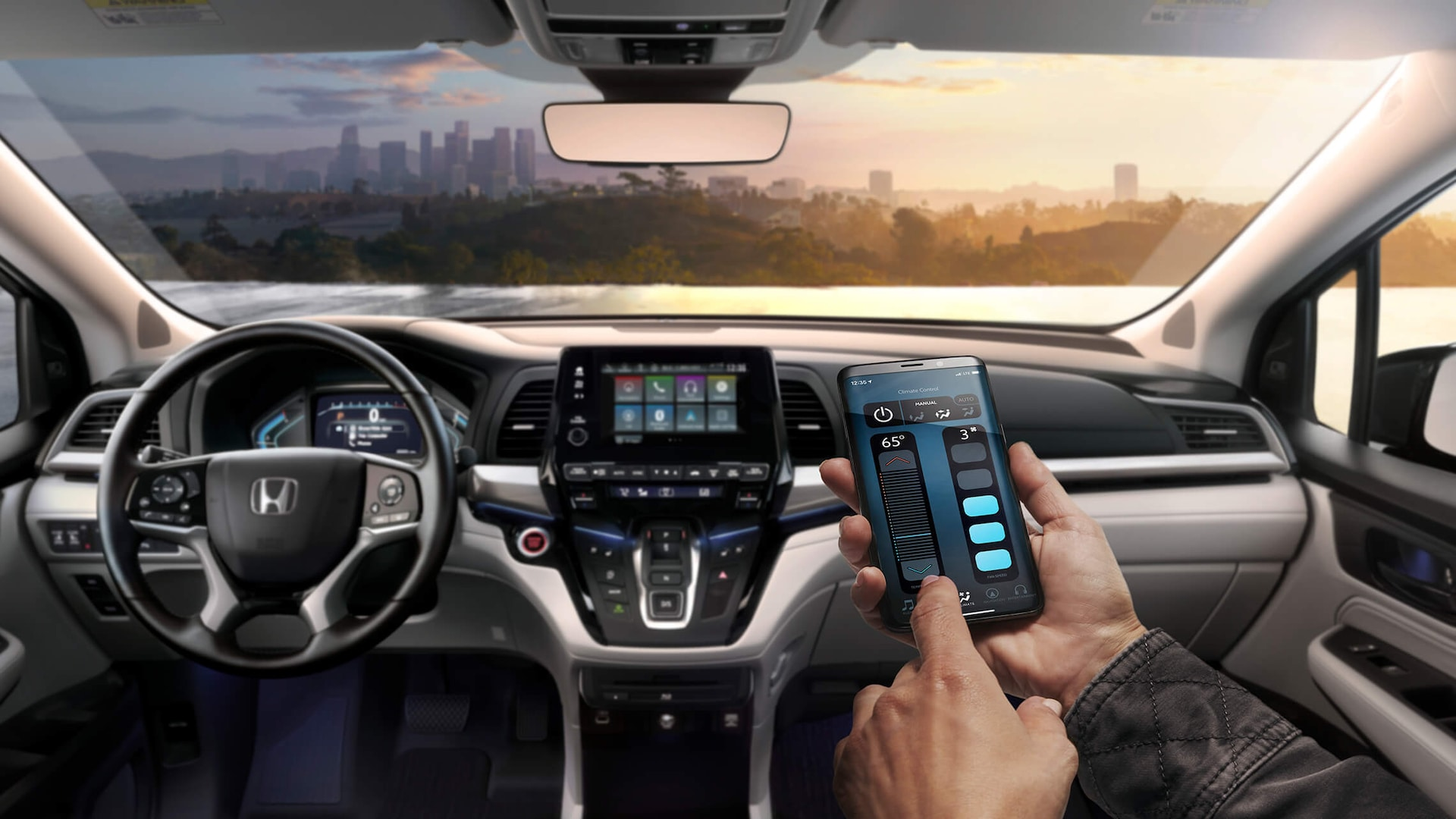 Close-up of a hand holding a smartphone, showing the CabinControl® app's climate control screen, in the 2021 Honda Odyssey.