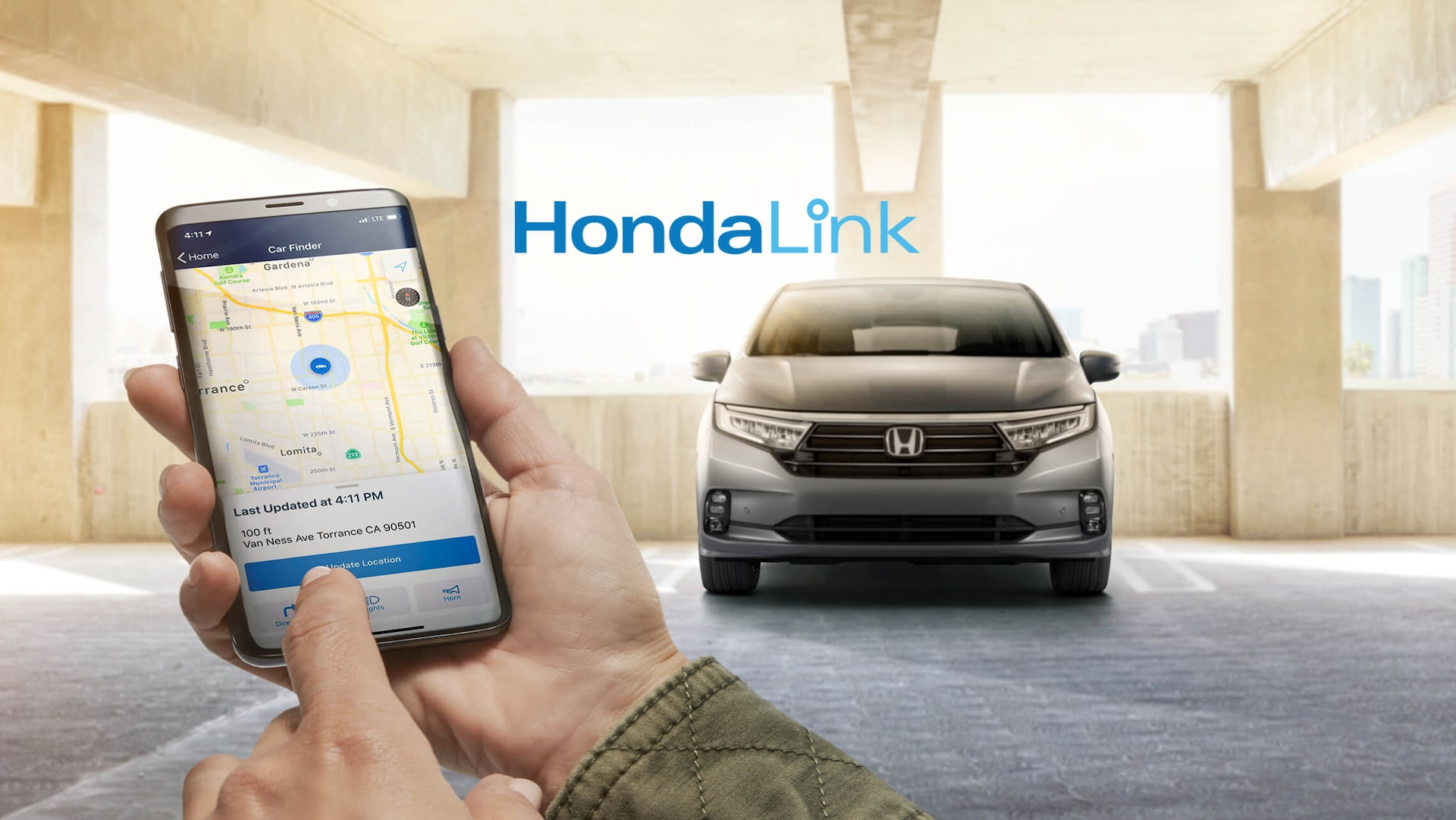 Close-up of a hand holding a smartphone, showing the HondaLink® app screen, with the 2022 Honda Odyssey parked in the background.