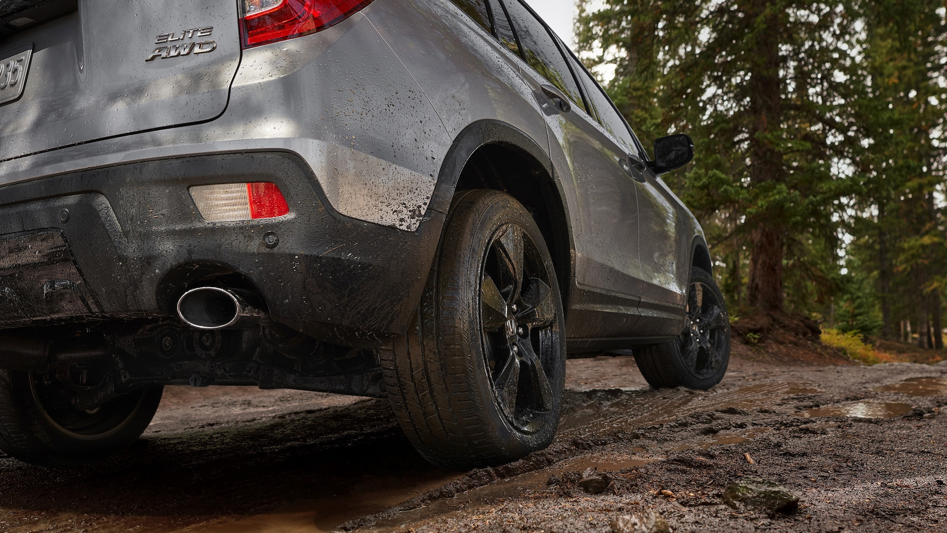 Passenger-side view of the 2021 Honda Passport Elite in Lunar Silver Metallic demonstrating all-season tires covered in mud on rocky terrain.