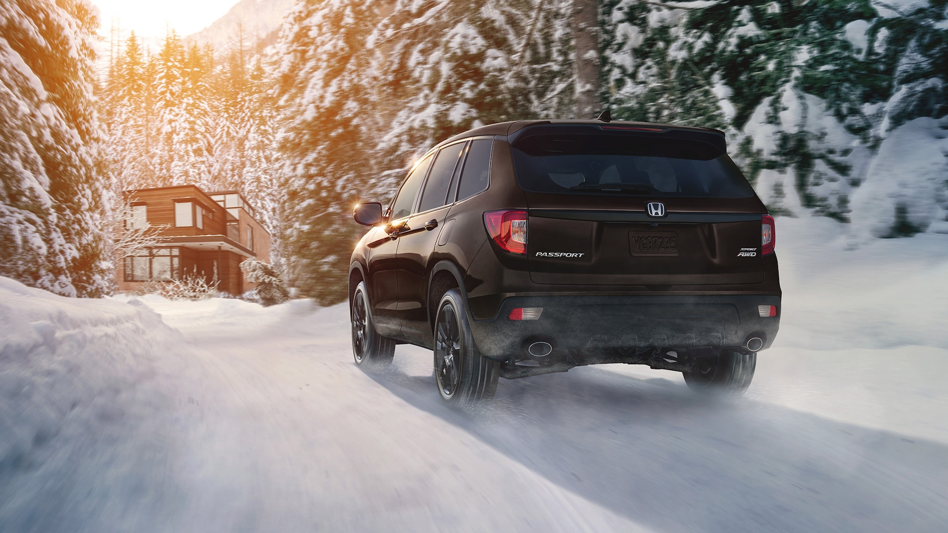 Driver-side rear view of the 2021 Honda Passport AWD Sport in Black Copper Pearl driving along a snowy forest road.