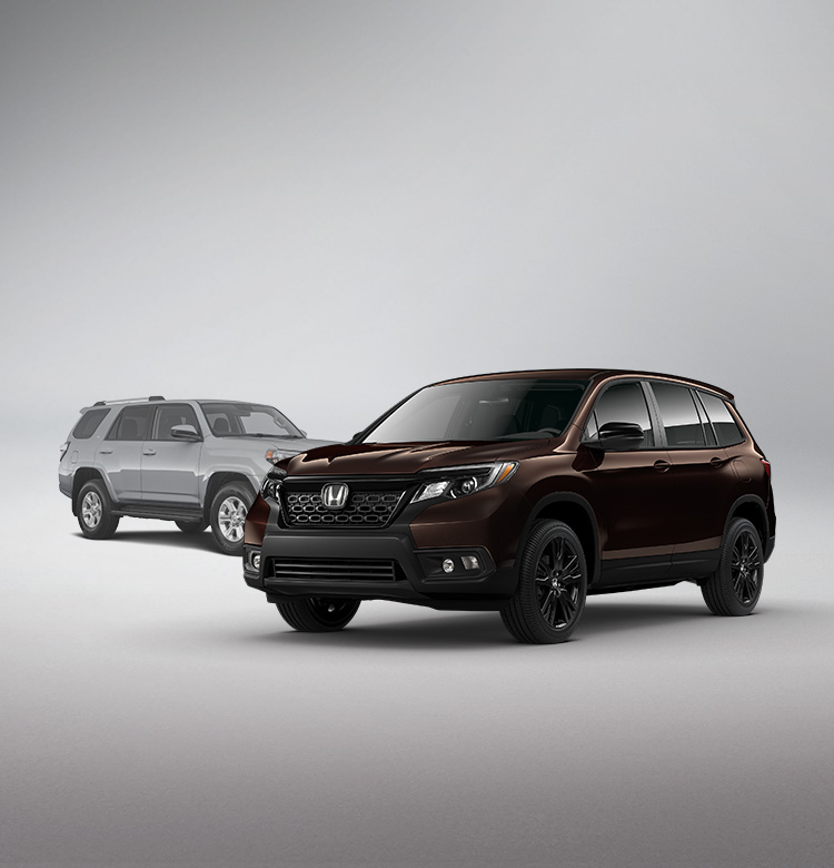 Front passenger-side view of the 2021 Honda Passport Sport in Black Copper Pearl parked in front of the 2020 Toyota 4Runner.